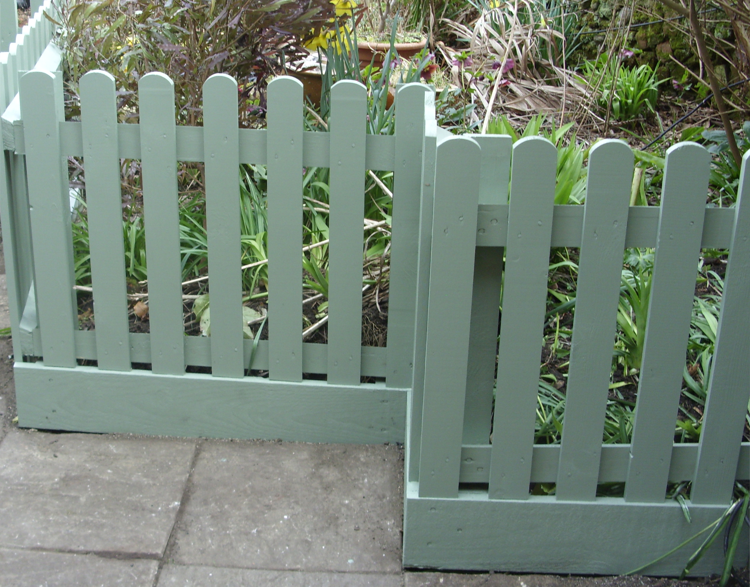 Planed round topped pickets with a retaining gravel board in Cuprinol shades - Willow